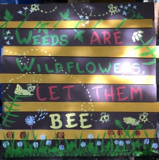 """My display sign for markets reads, """"weeds are wildflowers, let them Bee"""""""